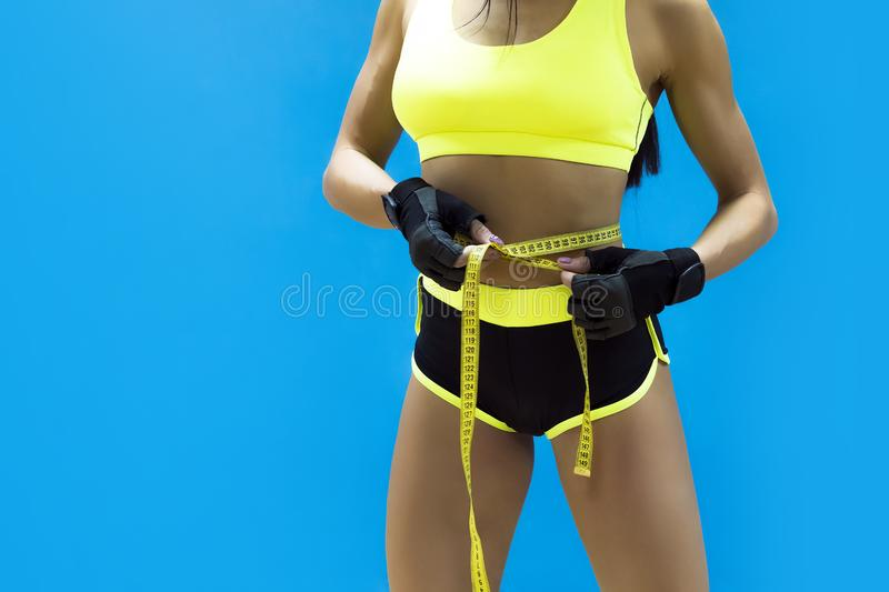 Crop shot of female bodybuilder with tape measure on waist on the blue background. Muscular body of a woman in sportswear with stock photo