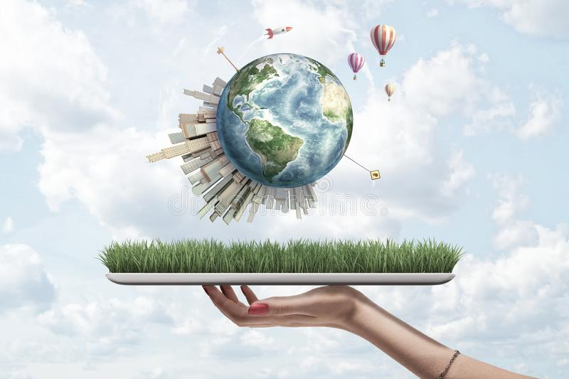 Crop side view of woman`s hand holding digital tablet with grass on screen and little Earth above with skyscrapers on stock photo