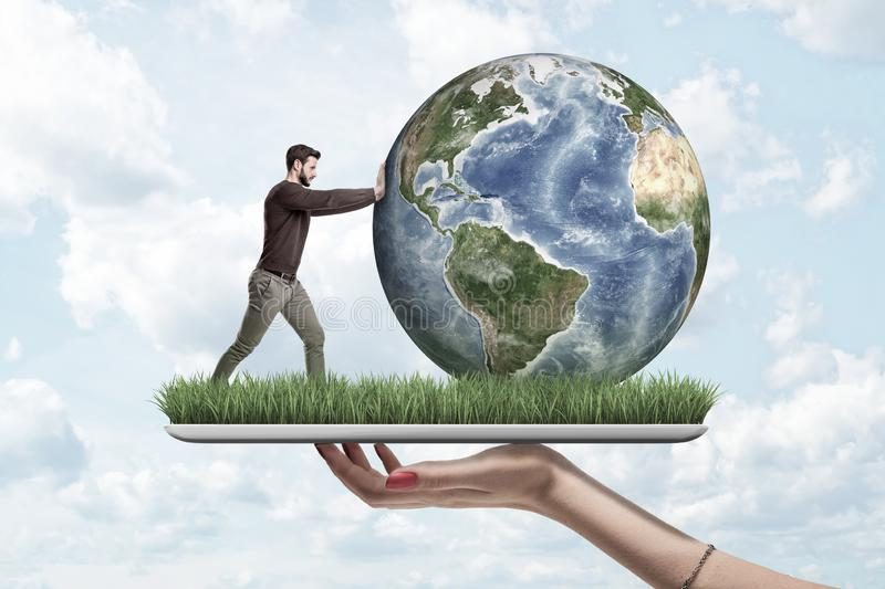 Crop side view of woman`s hand holding digital tablet with green grass growing on screen and little man pushing planet vector illustration