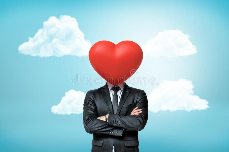 Crop view of businessman with arms folded and red heart instead of his head against blue sky with white clouds. royalty free stock images