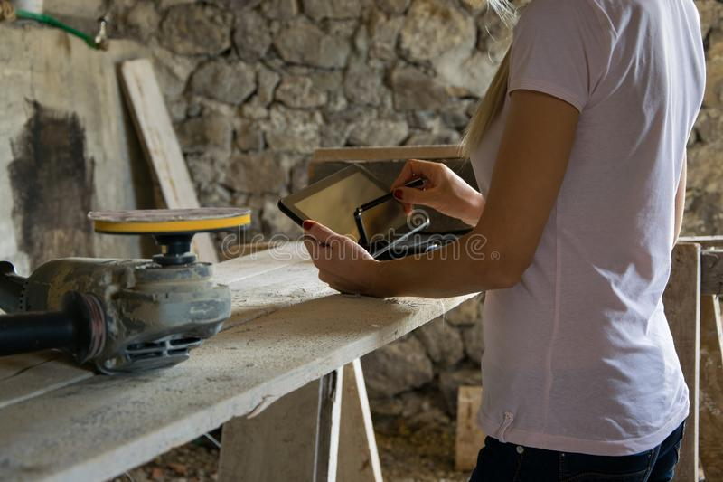 Crop view of female young adult with portable information device. In hand makes a project in a carpentry workshop stock photography
