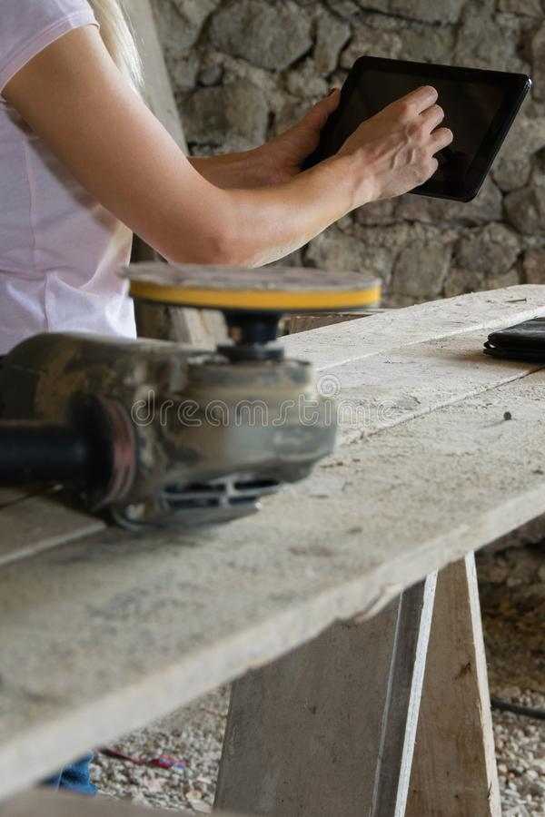 Crop view of female young adult with portable information device. In hand makes a project in a carpentry workshop stock images