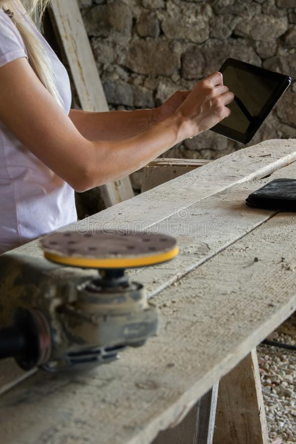 Crop view of female young adult with portable information device. In hand makes a project in a carpentry workshop royalty free stock image