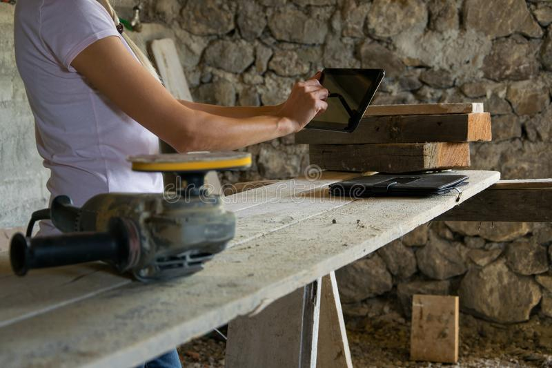 Crop view of female young adult with portable information device. In hand makes a project in a carpentry workshop stock image