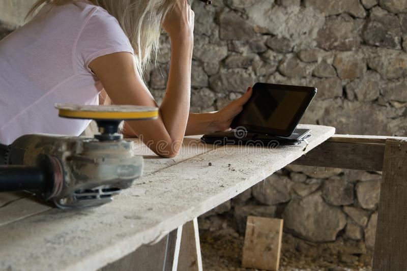 Crop view of female young adult with portable information device. In hand makes a project in a carpentry workshop royalty free stock photography