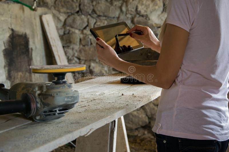 Crop view of female young adult with portable information device. In hand makes a project in a carpentry workshop royalty free stock photos