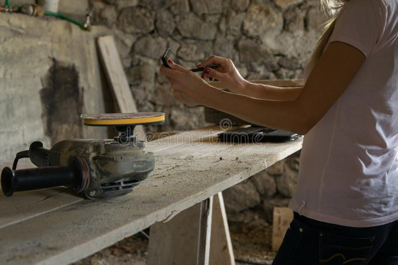 Crop view of female young adult with portable information device. In hand makes a project in a carpentry workshop royalty free stock photo