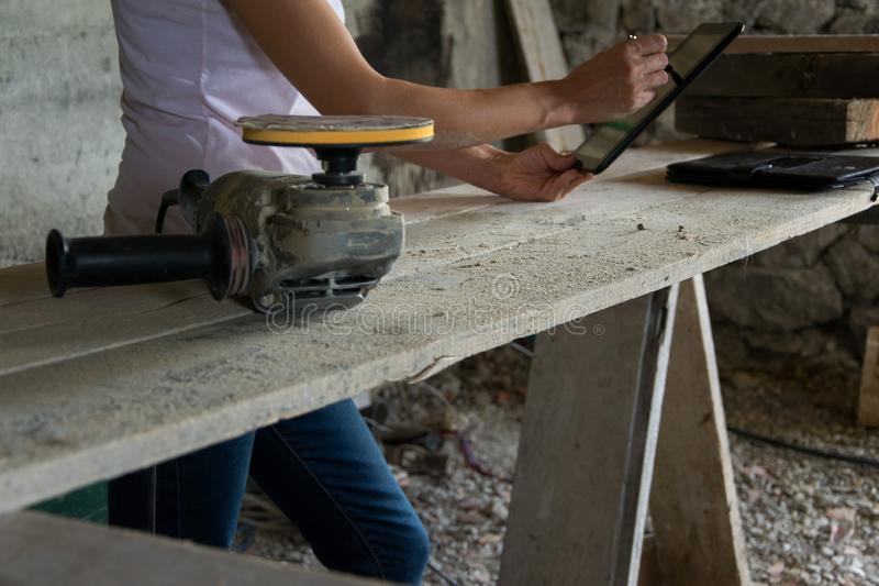 Crop view of female young adult with portable information device. In hand makes a project in a carpentry workshop stock photo