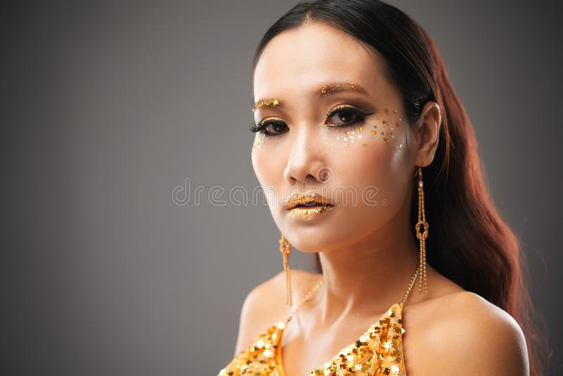 Beautiful ethnic woman with festive glitter makeup stock photography