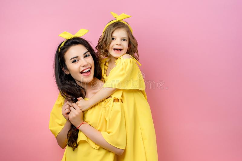 Young woman with cute child posing in yellow dresses stock photography