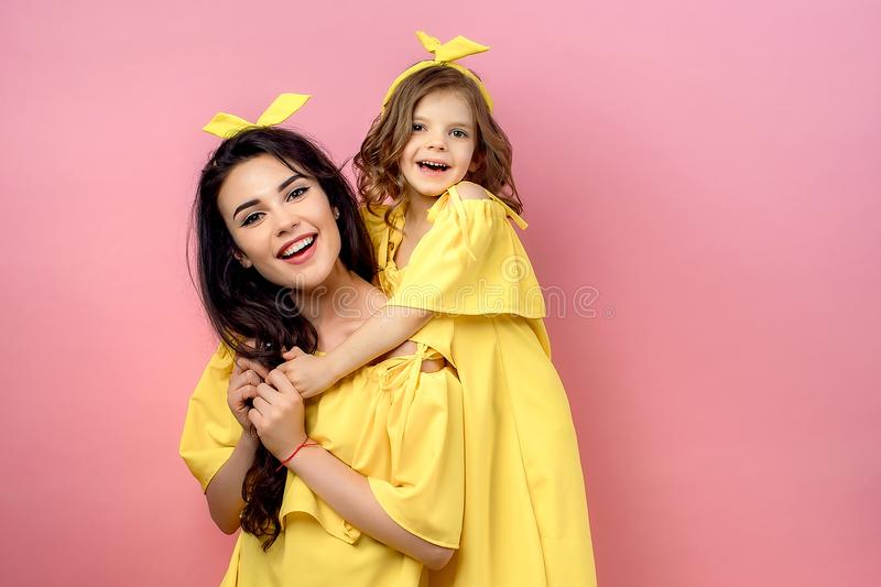 Young woman with cute child posing in yellow dresses stock image