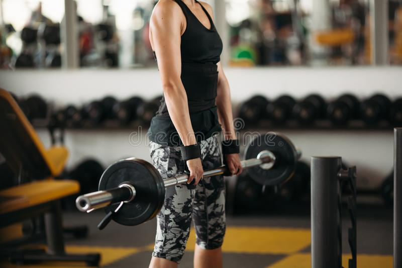 Crop of young and strong woman with athletic body doing exercises with barbell. stock photography