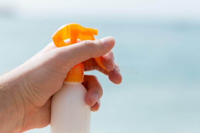 Croped bild av kvinnas hand som rymmer sunscreensprej på havsbakgrunden arkivbilder
