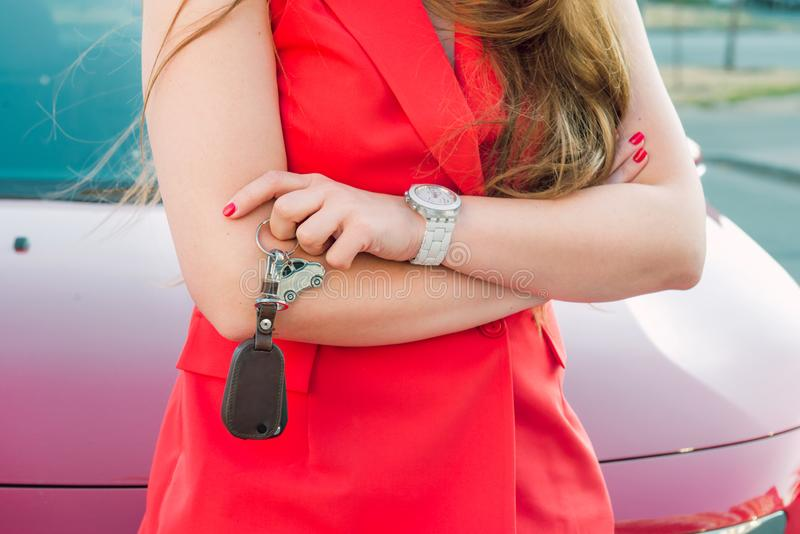 Croped, no face successful caucasian young business woman driver in red clothes holding car shaped keychain with keys standing on. The background of her red car royalty free stock images
