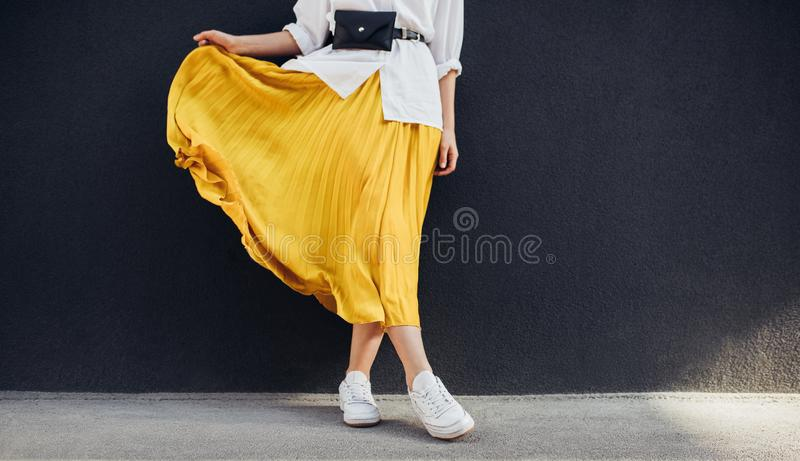 Cropped body shot of attractive woman in beautiful yellow skirt. Caucasian female fashion model standing over gray wall background. Outdoor with copy space stock images
