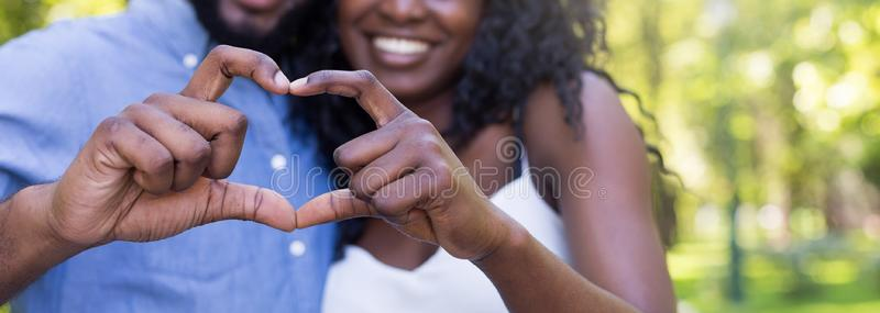 Cropped close up of couple making heart shape with hands stock photo