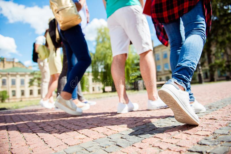 Cropped close up low angle photo shot of six student`s legs, walking on the cobbles. Sunny spring day, students are going to camp royalty free stock photography