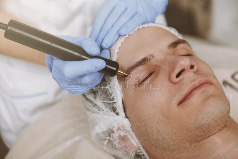 Handsome man getting facial skincare treatment royalty free stock image