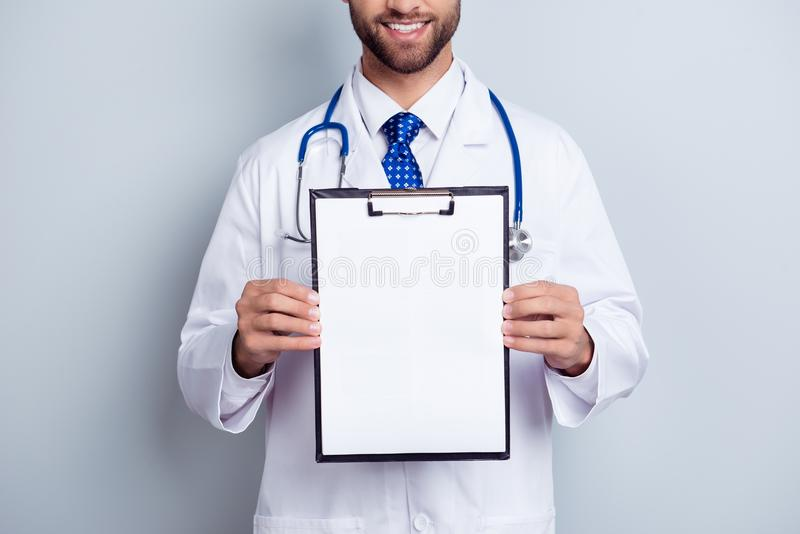 Cropped close up photo of bearded smiling intern, who is holding. The clipboard with empty paper. Doc is wearing white uniform and a tie, stands on a light stock photos