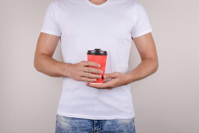 Cropped close up photo of bright vivid red cup with cap brown plastic lid in hands of handsome mach virile masculine cool man royalty free stock photos