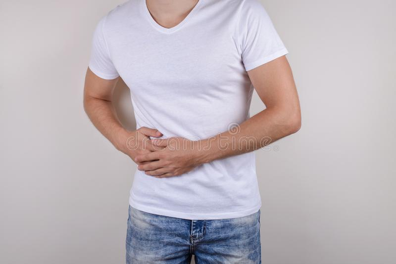 Cropped close up photo portrait of unhappy sad upset guy holding touching right side wearing casual t-shirt denim trousers isolate royalty free stock image