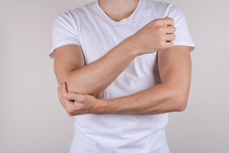 Cropped close up photo portrait of unhappy upset sad guy holding touching painful elbow wearing white t-shirt isolated grey backgr. Ound copy space royalty free stock images