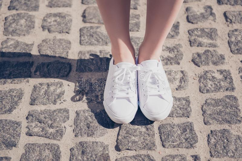 Cropped close up photo shot of a girl`s legs in white gumshoes o royalty free stock image