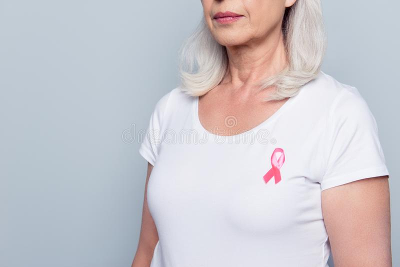 Cropped close up portrait of half turned aged woman in white t-shirt with breast cancer pink ribbon and serious expression over g stock images