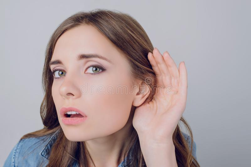 Cropped close up portrait of sad upset frustrated beautiful attractive charming woman carefully listening to gossip isolated on g stock image