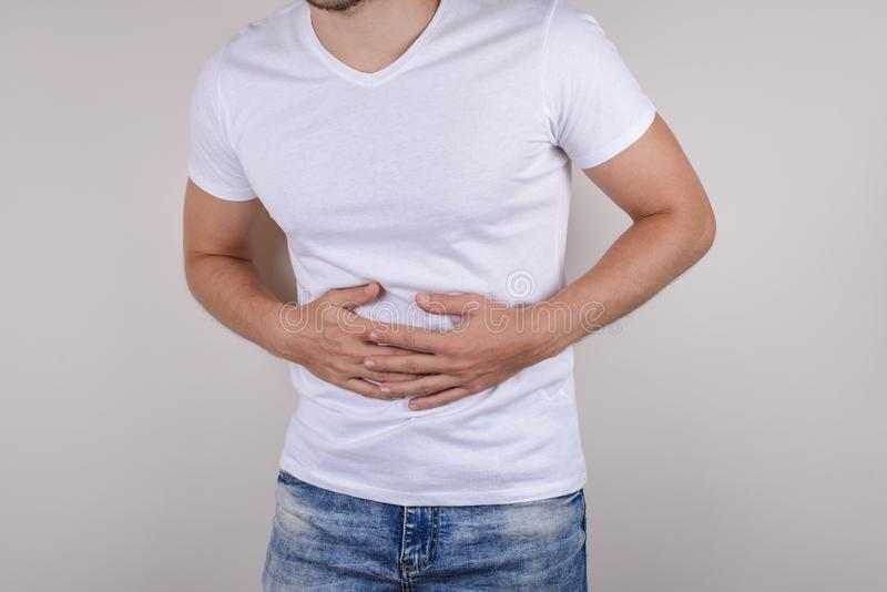 Cropped close up studio photo portrait of upset sad scared worried troubled gut having stomach ache disorder wear denim pants isol. Ated grey background stock photo