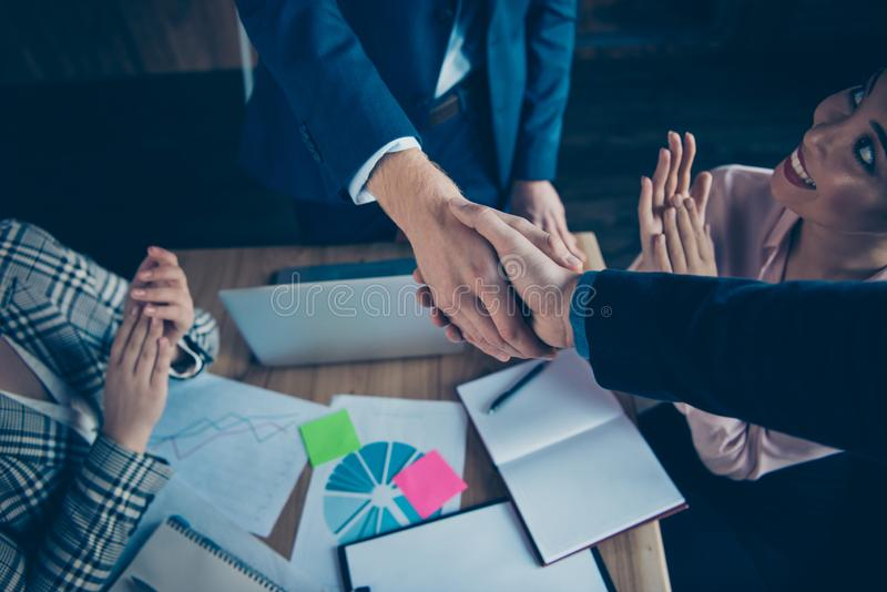 Cropped close-up view of hands shake nice chic cheerful business sharks experts welcome new participant congrats. Greetings over desktop at modern industrial stock images