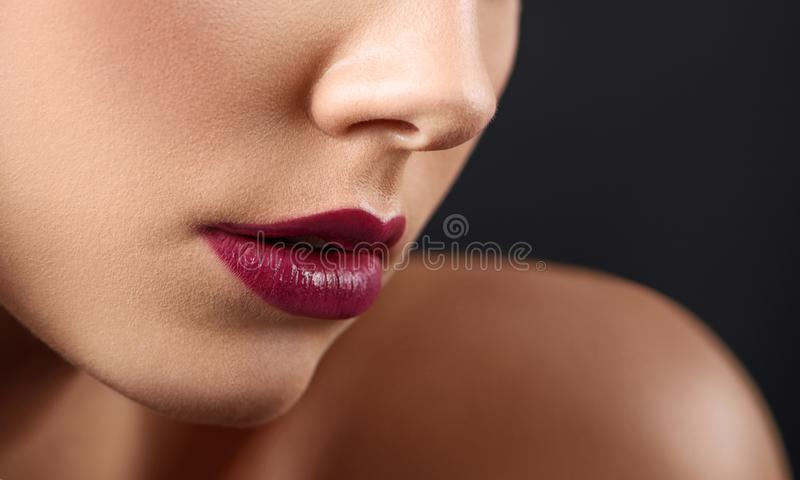 Cropped close up of woman`s lips covered with dark lipstick. stock photo