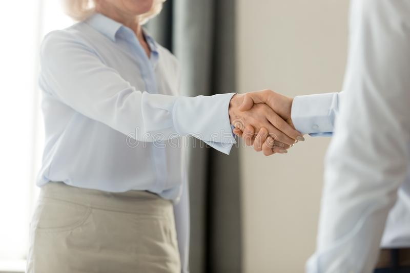 Cropped closeup image middle aged business lady handshake with businessman. Cropped close up image middle aged business lady greeting corporate client shake royalty free stock photo