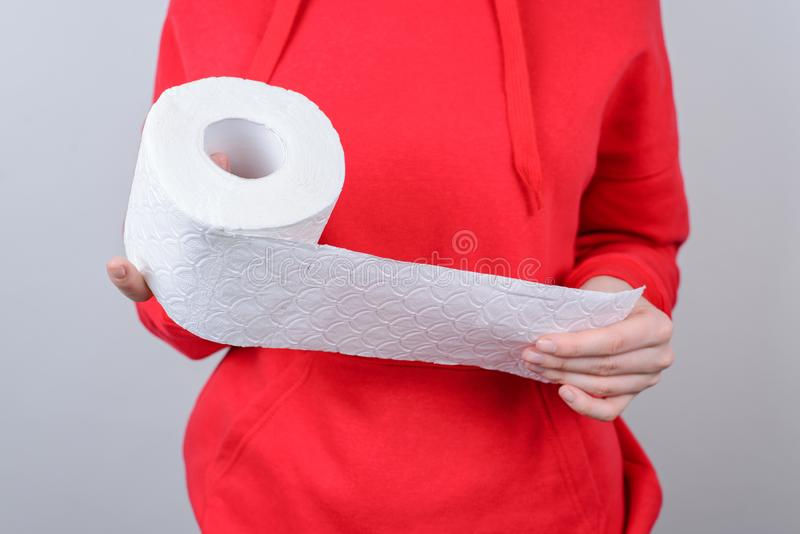 Cropped closeup photo picture of serious unhappy upset sad she people use take give white soft toilet paper in hand wear red royalty free stock photos