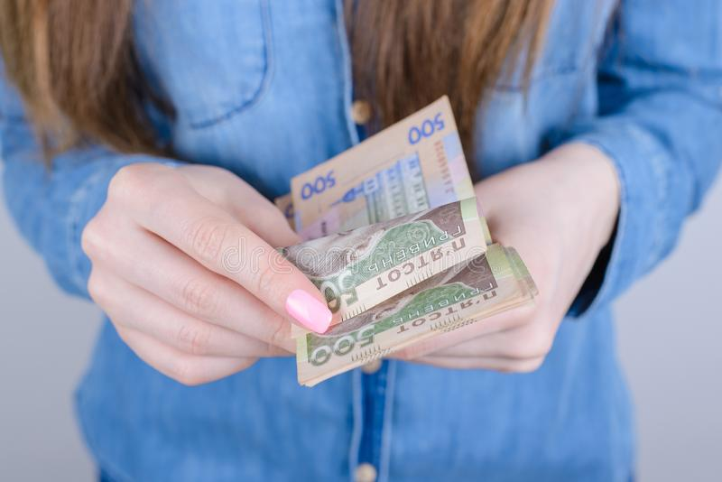 Cropped closeup photo portrait of serious wealthy rich lady getting large high salary wage holding in hands  grey. Background royalty free stock photo