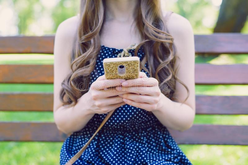 Cropped closeup photo of slim lovely pretty attractive teen lady user holding telephone in golden case in hands reading latest stock photography
