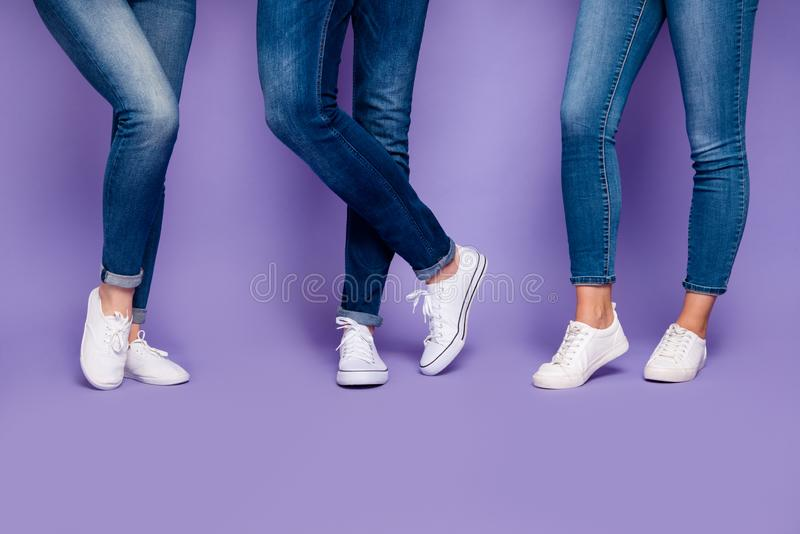 Cropped closeup photo of three people`s legs wearing denim dark blue jeans trousers pants standing on the floor isolated royalty free stock photography