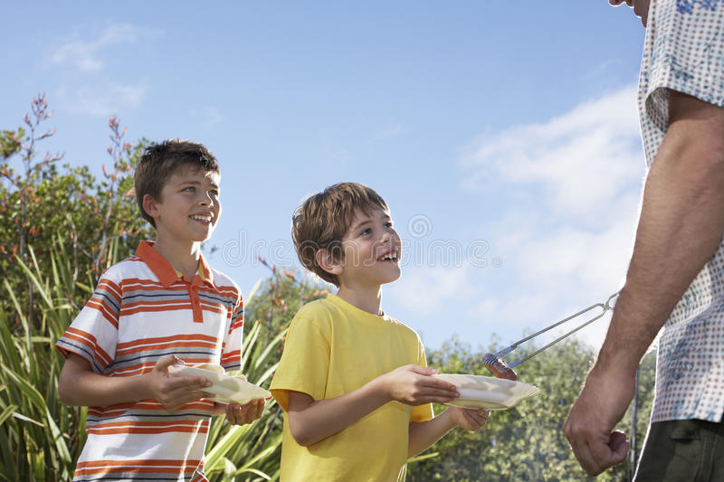 Cropped Father Serving Grilled Frankfurters To Sons Outdoors stock images