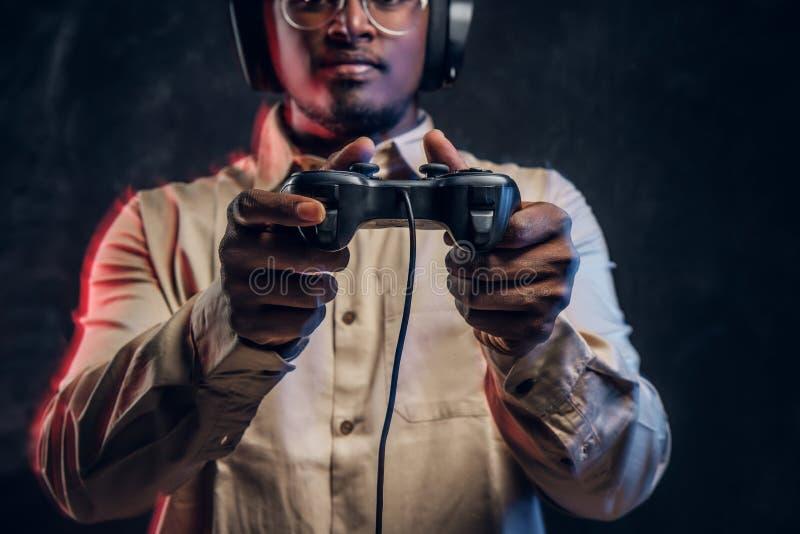 Cropped fotografia ciemnoskóry gracz z hełmofonami i gemowym joystickiem zdjęcia stock