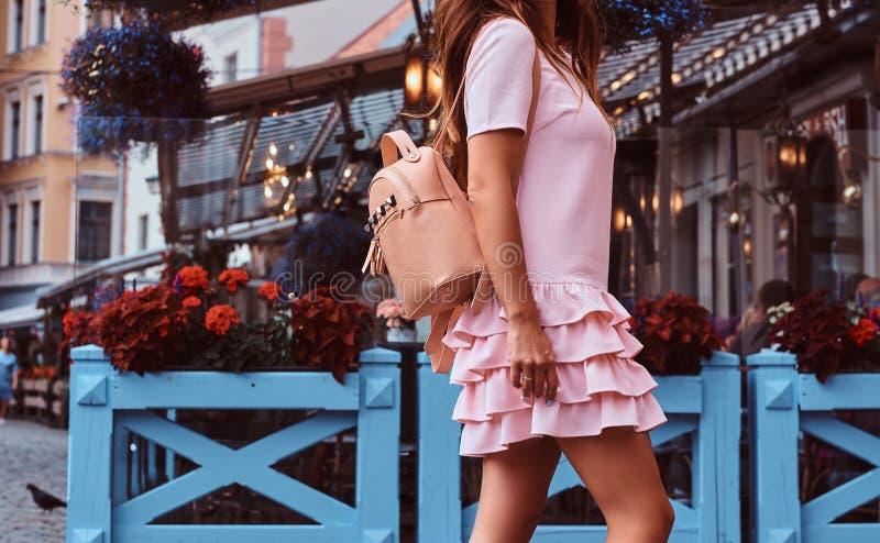 Cropped fotografia Kobieta z długim brown włosy ubierał w menchii sukni z plecak pozycją blisko tarasowej kawiarni fotografia stock