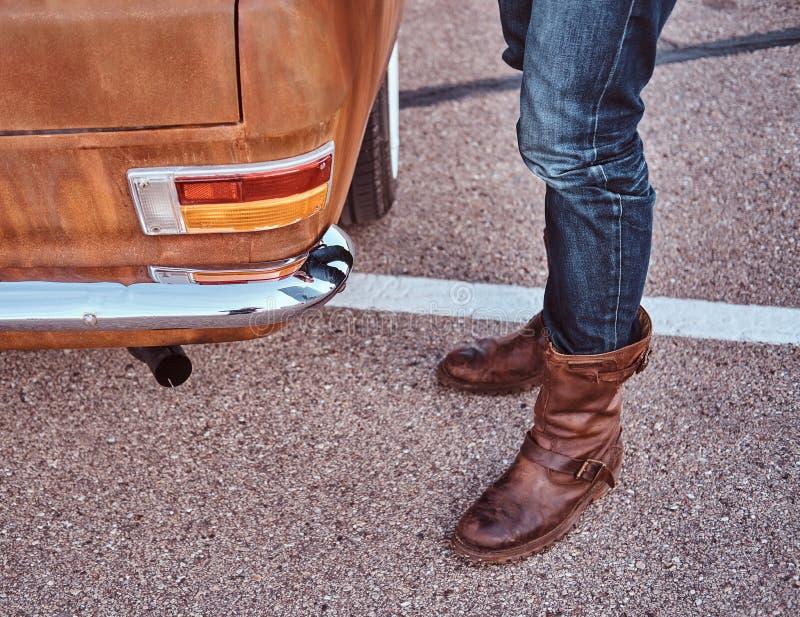 Cropped fotografia samiec stoi blisko retro samochodu w miasto parking w cajgach i butach fotografia royalty free