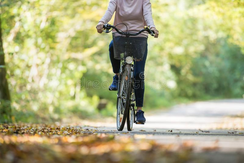 Cropped view of an active woman riding a bicycle stock photos