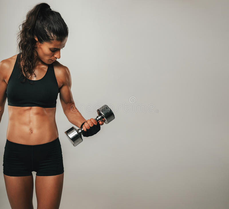 Cropped front view of woman lifting dumbbell. Cropped front view of woman in black shorts and weight training gloves lifting single dumbbell with bicep muscles royalty free stock photos