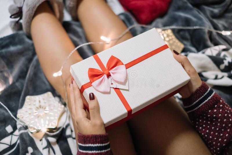 Cropped girl holding present over her nude calfs royalty free stock images