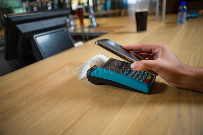 Cropped hand of customer making contactless payment. At wooden bar counter stock photo