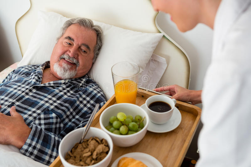Cropped hand of female doctor serving food to senior patient relaxing on bed stock images