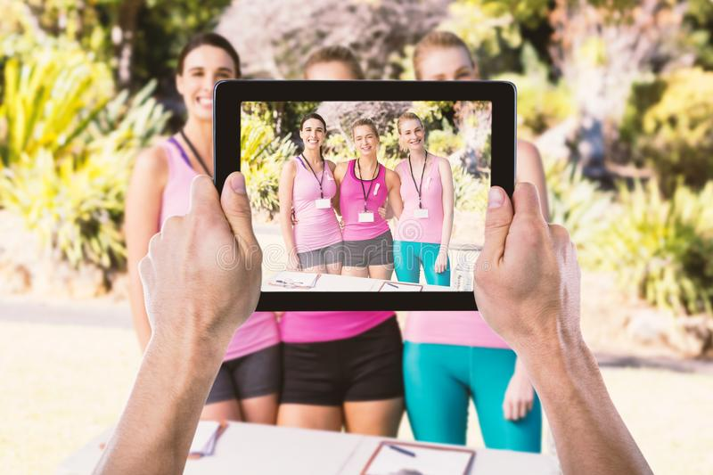 Composite image of cropped hand holding digital tablet. Cropped hand holding digital tablet against portrait of happy female volunteers standing in park stock photos
