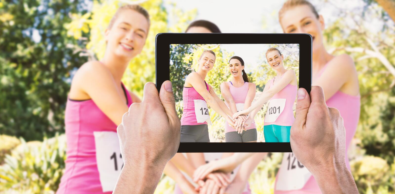 Composite image of cropped hand holding digital tablet. Cropped hand holding digital tablet against portrait of young athletes stacking hands stock photo