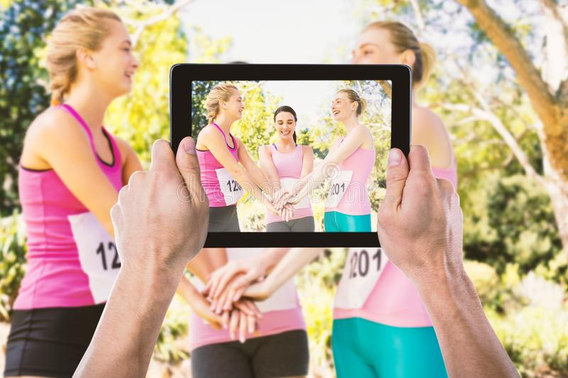 Composite image of cropped hand holding digital tablet. Cropped hand holding digital tablet against young female athletes stacking hands stock photos