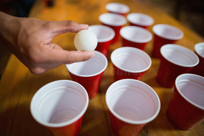 Cropped hand of man playing beer pong royalty free stock photo